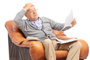 Shocked senior man looking at his bills in disbelief, have your utility bills jumped?